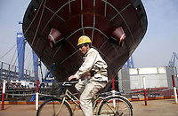 A Chinese worker rides his bicycle past a ship under construction at the Hudong Zhonghua Shipbuilding Co., LTD in Shanghai, China. China is the world's third largest shipbuilding nation after South Korea and Japan. While growing international interest in its lower building cost and domestic tanker demand to fulfill the country's hunger for energy is likely to push the country to the top position, the rapidly increasing price of steel has also undercut the industry's profitability..