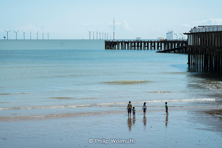 Children play on the beach by Clacton Pier and the London Array offshore wndfarm.  The resort is the second most deprived seaside town in the UK.
