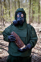 A member of the Belgian Unexploded Ordnance Disposal Group, wearing an NBC suit (Nuclear, Biological, Chemical), holds an unexploded shell. It is likely it is a mustard or phosgene gas shell. In Belgium munitions from WW1 still pose a large threat.
