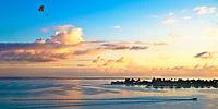 Sunset parasailing above overwater bungalows in Bora Bora lagoon, a beautiful honeymoon destination, near Tahiti, French Polynesia, Pacific Ocean