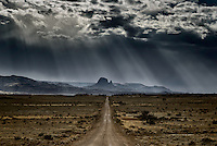 A remote road through the desert leading to a distant, mitten shaped rock formation, all under a stormy sky with sunbeams breaking through the cloud cover.