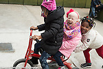 Education Preschool 4 year olds group of girls on playground having fun on tricycle one pedaling, one pushing, one riding