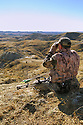 00105-040.04 Bowhunting (DIGITAL) A well-camouflage archer uses binoculars to spot game from ridge in Badlands.  Hunt, mule deer.  V4A1