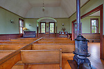 Church interior, with pot belly stove and pews.  Oysterville Babtist Church, circa 1872 was re-dedicated as an ecumenical church in 1981.  It is now managed by the Oysterville Restoration Foundation as a community resource.  Long Beach Peninsula, Washington State.  USA. HDR.