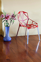 A contemporary red dining chair is juxtaposed with a vase of lilies on the wooden floor of the entrance hall