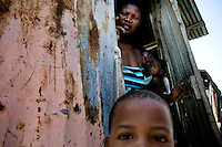 An abandoned wife, living alone with a lot of children, stands in the door of a shack in the slum of Cité Soleil, Port-au-Prince, Haiti, 9 July 2008. Haitian men leave their wifes with no legal obligations, giving them no support at all. The overall situation on Haiti gets worse every year and the extreme, hardly imaginable poverty hits more and more people. The Haitian economics is paralysed, there is no infrastructure, no food supplies, the population suffer from hunger, social and living conditions in Haitian slums (e.g. Cité Soleil) are a human tragedy. The rage grows and the tension continues with undiminished strength.