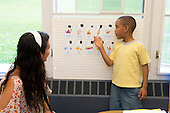 MR / Schenectady, NY. Zoller Elementary School (urban public school). Kindergarten classroom. Student (boy, 6, African American /  Puerto-Rican American) points to vocabulary word card during Spanish lesson for bilingual students taught by student teacher (Colombian-American). MR: Car38. ID: AM-gKw. © Ellen B. Senisi.
