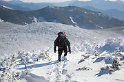 Winter hiker on the summit of South Twin Mountain in the White Mountains, New Hampshire USA during the winter months. Windy conditions cause snow to blow around. The Appalachian Trail crosses the summit of South Twin Mountain.