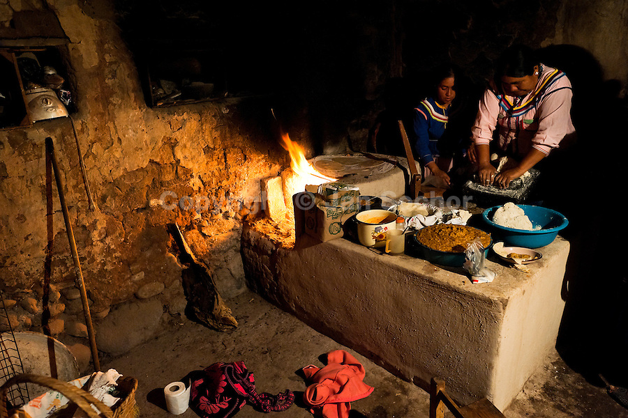 """Cora Indian women prepare tortillas in the kitchen before the religious ritual celebration of Semana Santa (Holy Week) in Jesús María, Nayarit, Mexico, 21 April 2011. The annual week-long Easter festivity (called """"La Judea""""), performed in the rugged mountain country of Sierra del Nayar, merges indigenous tradition (agricultural cycle and the regeneration of life worshipping) and animistic beliefs with the Christian dogma. Each year in the spring, the Cora villages are taken over by hundreds of wildly running men. Painted all over their semi-naked bodies, fighting ritual battles with wooden swords and dancing crazily, they perform demons (the evil) that metaphorically chase Jesus Christ, kill him, but finally fail due to his resurrection. La Judea, the Holy Week sacred spectacle, represents the most truthful expression of the Coras' culture, religiosity and identity."""