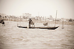 A fisherman works the waters off the coast of Benin, capital city of Cotonou in the background.