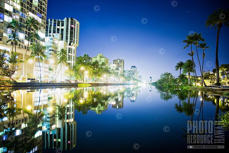 A reflection of Waikiki buildings and trees at the edge of the Ala Wai Canal, Honolulu, O'ahu.