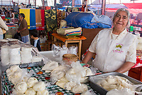 Tlacolula; Oaxaca; Mexico.  Tlacolula Market.  Woman Selling Oaxacan String Cheese in Plastic Bags.