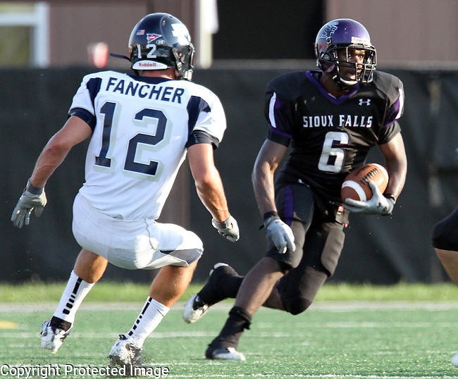 SIOUX FALLS, SD - SEPTEMBER 1: Michael Hicks #6 of the University of Sioux Falls looks for running room past Mark Fancher #12 from Washburn University on a punt return in the first quarter of their game Thursday night at Bob Young Field in Sioux Falls.  (Photo by Dave Eggen/Inertia)