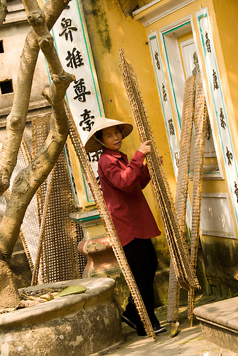 A woman works with the drying racks for rice paper. Chinese writing and influence can be seen in the background.  At one time Vietnam didn't produce enough rice to feed itself, but with the introduction of the free market they've soared to become one of the top exporters in the world.