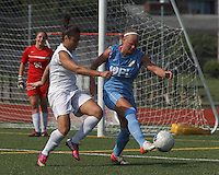 Seacoast United Mariners defender Ida Bjerklund (20) clears the ball as Boston Aztec forward Sonia Basma (8) defends. In a Women's Premier Soccer League (WPSL) match, Boston Aztec (white) defeated Seacoast United Mariners (blue), 2-1, at North Reading High School Stadium on Arthur J. Kenney Athletic Field on on June 23, 2013. Due to injuries through the season, Seacoast United Mariners could only field 10 players.