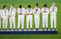 YOKOHAMA, JAPAN - AUGUST 6: The USWNT stands on the podium at International Stadium Yokohama on August 6, 2021 in Yokohama, Japan.