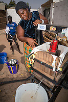 Using an Automobile Jack, the Woman presses fermenting cashew apples to collect their juice in a container below the press.  The juice will later be heated to speed its conversion to alcohol.  North Bank Region, The Gambia.  The woman is of the Manjago ethnic group, a primarily Christian tribe.