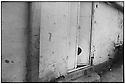Uzbekistan - Bukhara - Little girl hiding behind the door of her house.