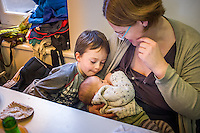 A mother breastfeeding her baby in a museum cafe while her older son talks to the baby.<br /> <br /> London, England, UK<br /> 08/03/2015<br /> <br /> © Paul Carter / wdiip.co.uk