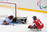 Sochi, RUSSIA - Mar 15 2014 - Greg Westlake takes a shot on Kristian Buen as Canada takes on Norway in the Bronze Medal Sledge Hockey game  at the 2014 Paralympic Winter Games in Sochi, Russia.  (Photo: Matthew Murnaghan/Canadian Paralympic Committee)