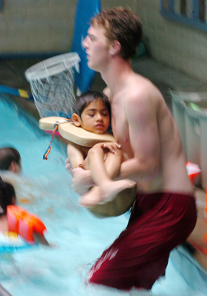 James Finster, Aquidic Specialist at Mary Lou Clack Pool in Vista,  carries Jorge Levi  in the therapy swimming pool during a swim class for special education students at the Mary Clack Therapy Pool located in Vista