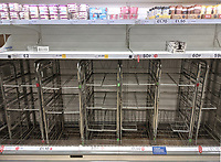 Shoppers queue just after dawn at this Tesco superstore in Kettering, Northants. Shelves are already empty and signs are up asking shoppers to be polite to staff and to address 'social distancing'. Kettering, UK Saturday March 21st 2020<br /> <br /> Photo by Stuart Hogben