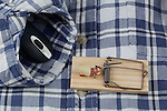 Mouse trap and computer mouse on mens flannel shirt.  Trapped.   Generic mouse traps in clean cut, white background.