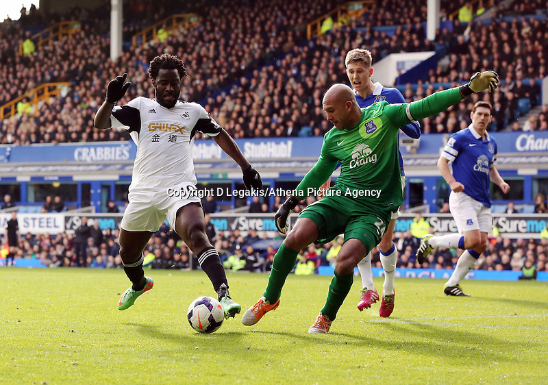 Pictured L-R: Wilfried Bony of Swansea has his shot stopped by Everton goalkeeper Tim Howard. Saturday 22 March 2014<br /> Re: Barclay's Premier League, Everton v Swansea City FC at Goodison Park, Liverpool, UK.