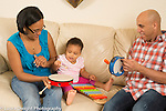 18 month old toddler girl at home with parents playing musical instruments together