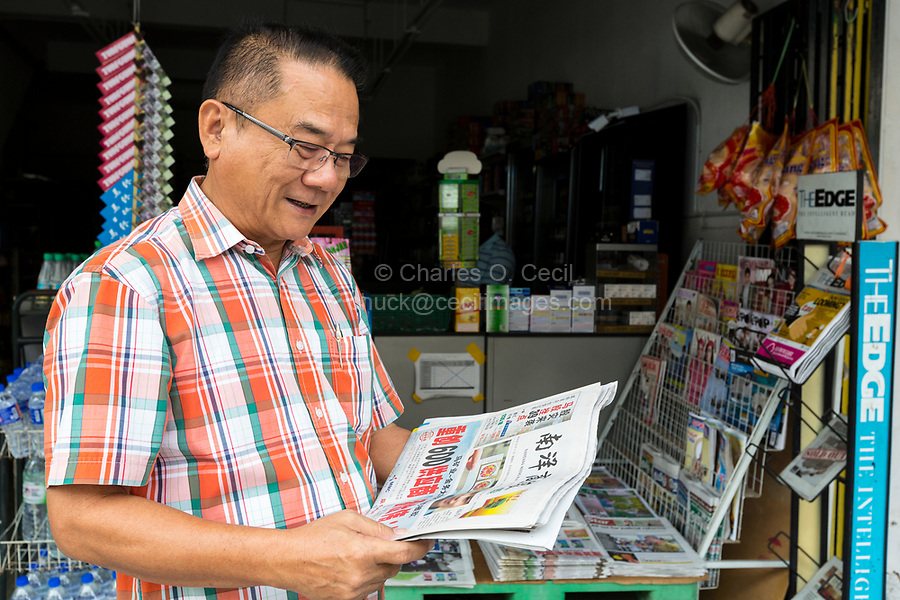 Middle-aged Man Reading Chinese-language Newspaper, Ipoh, Malaysia.