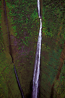 Close-up of a gorgeous white waterfall cutting through the mountain on the lush, remote Waipio Valley on the Hamakua coast of the Big Island of Hawaii.