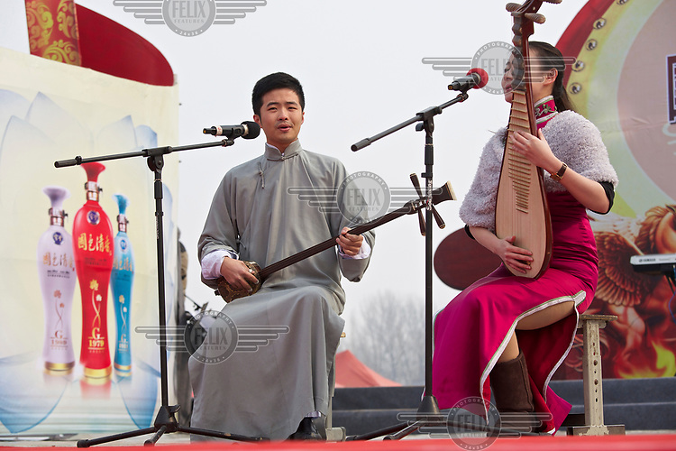 Traditional storytellers, playing Chinese musical instruments, performs at the Ma Jie folk festival. <br /> <br /> For centuries farmers in Henan have gathered during Chinese New Year in the region's wheat fields to listen to bards singing and recounting old tales. <br /> <br /> Now storytellers come from all over China to attend the annual festival where large crowds gather to watch the best performers.
