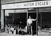 BNPS.co.uk (01202 558833)<br /> Pic: RayFisher/BNPS<br /> <br /> Pictured: Ray outside in his shop at opening time in 1959.<br /> <br /> Tireless Ray Fisher still works full-time in the motorcycle shop he opened 62 years ago - and he has plenty left in the tank.<br /> <br /> The 85 year old founded Ray Fisher's Brickbits in Christchurch, Dorset, in 1959 after training as a bike mechanic.<br /> <br /> It is a family affair as his two children Gerry, 58, and Stephanie, 54, have both worked solely for him since leaving school aged 16.<br /> <br /> Ray said he had loved bikes since childhood and learnt how to repair them while doing national service in the early 1950s.