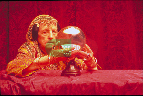 elder woman telling fortune with crystal ball