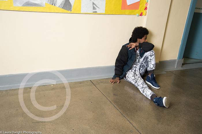 Education HIgh School isolated teenage boy sitting alone in corridor