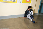 Education HIgh School isolated teenage boy sitting alone in corridor