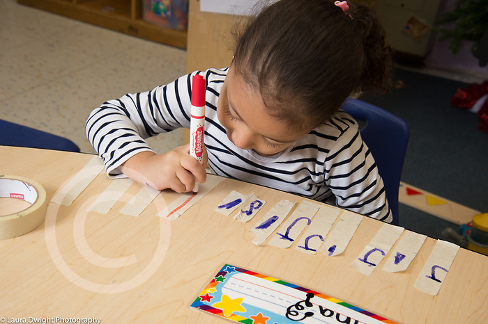 Education Preschool 3-4 year olds girl at table writing letters on pieces of tape using marker
