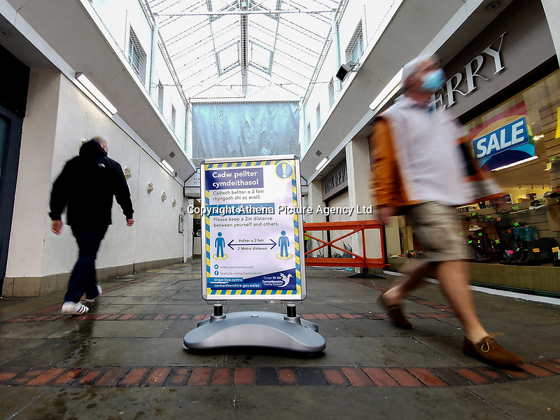 Pictured: Two men walk past a social distancing sign in Llanelli Town Centre, Llanelli, Wales, UK. Sunday 27 September 2020<br /> Re: Local lockdown will be in force from 6pm on the 27th of September, due to the Covid-19 Coronavirus pandemic, in Llanelli, Wales, UK