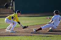Michigan Wolverines third baseman Jacob Cronenworth (2) tags out Texas State base runner Garrett Mattlage (3) during the NCAA season opening baseball game against the Texas State Bobcats on February 14, 2014 at Bobcat Ballpark in San Marcos, Texas. Texas State defeated Michigan 8-7 in 10 innings. (Andrew Woolley/Four Seam Images)
