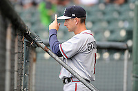 Manager Jonathan Schuerholz (2) of the Rome Braves gives signs to his team in the rain in a game against the Greenville Drive on Thursday, July 31, 2014, at Fluor Field at the West End in Greenville, South Carolina. Rome won the rain-shortened game, 4-1. (Tom Priddy/Four Seam Images)