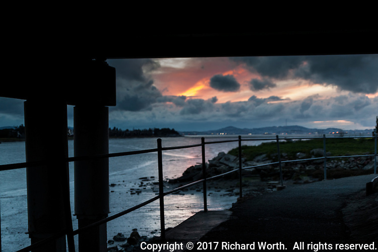 The distant sunset's glow shines through the closer storm clouds.  The view from the trail passing under the north side of the Bay Farm Bridge where San Leandro Bay flows into San Francisco Bay - Alameda, California.
