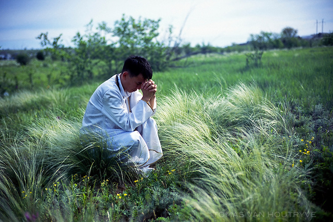 """Memebers of the """"Rebirth"""" religious community participate in a ceremony in the middle of a field that they consider to have sacred magnetic powere on the outskirts of Elista, Republic of Kalmykia, Russian Federation on May 15, 2010. The unusual religious sect combines believes from multiple major religions as well as paranormal beliefs in extra-terrestrials, UFOs and cosmic powers. Among those that have participated in their ceremonies is Kalmyk president Kirsan Ilyumzhinov, who has stated on Russian national television that he believes he was abducted by aliens."""