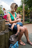 A mother breastfeeds her little boy in the playground of her local park.<br /> <br /> Hampshire, England, UK<br /> 03/09/2014<br /> <br /> © Paul Carter / wdiip.co.uk