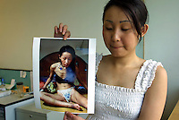 Ah Li, a 21 year-old female drug addict looks back at her old photos, after receiving treatment in the drug rehabilitation centre in Bao'an. Ah Li moved to Shenzhen from northern China when just sixteen years old after the break-up of her family. She was tricked into prostitution and initially forced to take drugs until she became addicted and dependent on her gang bosses.