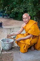 Cambodia, Bayon.  Buddhist Monk Placing Incense Sticks.