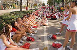 The University of Wisconsin cheerleaders anxiously relax alongside band members in the shade of palm trees from the Florida heat. Temperatures were reaching as high as 86 degrees during the duration of the parade.