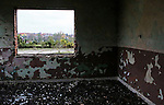 A look through the window of an abandoned school toward Dunavtsi, a town of waning population in Bulgaria, on October 27th, 2014. Bulgaria has the most extreme population decline in the world — much of it due to post-1989 emigration, high death rates and low birth rates. There are so few people of child-bearing age in the nation that population statistics project a 30-percent decrease by 2060, from 7.2 million to just over 5 million. In other words,Bulgaria's population declines by 164 people a day, or 60,000 people a year — 60 percent of them aged over 65.<br /> <br /> This photo is from a project that aims to gauge the state and effect of democracy in the former Soviet satellite nation Bulgaria, two and a half decades after the fall of the Berlin Wall. The story of democracy in Bulgaria at age 25 is a cautionary tale about transplanting one-size-fits-all Western values to a nation still undergoing social and economic upheaval. Bulgaria is still one of the poorest, most corrupt nations in the European Union, its post-1989 hopes wilted by political instability, high crime rates and skyrocketing inflation. While Bulgarians can now freely vote and protest without much threat to their freedom, their new oppressor is corruption - which is at a 15 year high, across political and civil sectors alike. The ennui is so casually etched on the passerby's face that it becomes routine - one that fits in sadly well against a startling backdrop of rotting architecture, joblessness, and a vast population decline. Despite what democracy has changed in Bulgaria, the daily struggles of its populace remain largely untouched, trapped in a post-communist time capsule.