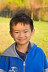 Vietnamese American second grade male smiles looking at camera in headshot outdoors in school yard