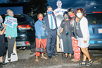 """Boston Mayor Marty Walsh (blue facemask) poses with attendees and cardboard cutouts of Barack Obama and Hillary Clinton as people gather to watch the 2020 Democratic National Convention at a """"Ridin' with Biden"""" Drive-In Theater viewing event at Suffolk Downs in Boston, Massachusetts, on Wed., Aug. 19, 2020."""