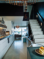 The open plan kitchen and living area stretches the length of the loft apartment
